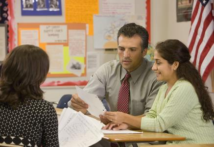 Parents with teacher reviewing student work