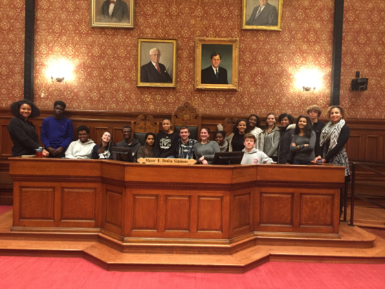 Members of the 2015-16 Cambridge Youth Council sitting at the mayor's desk.